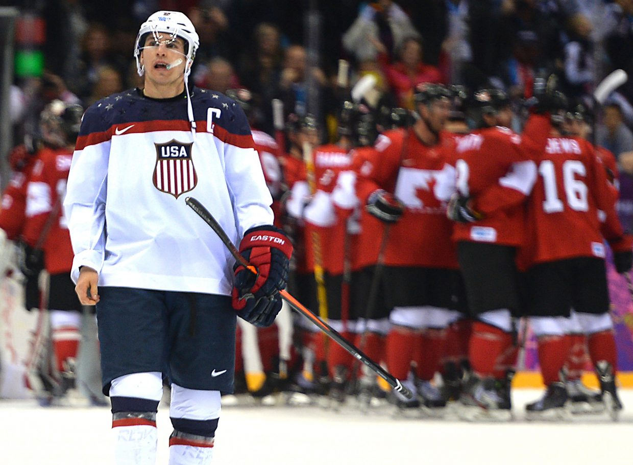 U.S. captain Zach Parise skates away from the celebrating Canadians on Friday after Team USA fell in the Olympic men's hockey semifinals, 1-0, to the neighbors from the north.