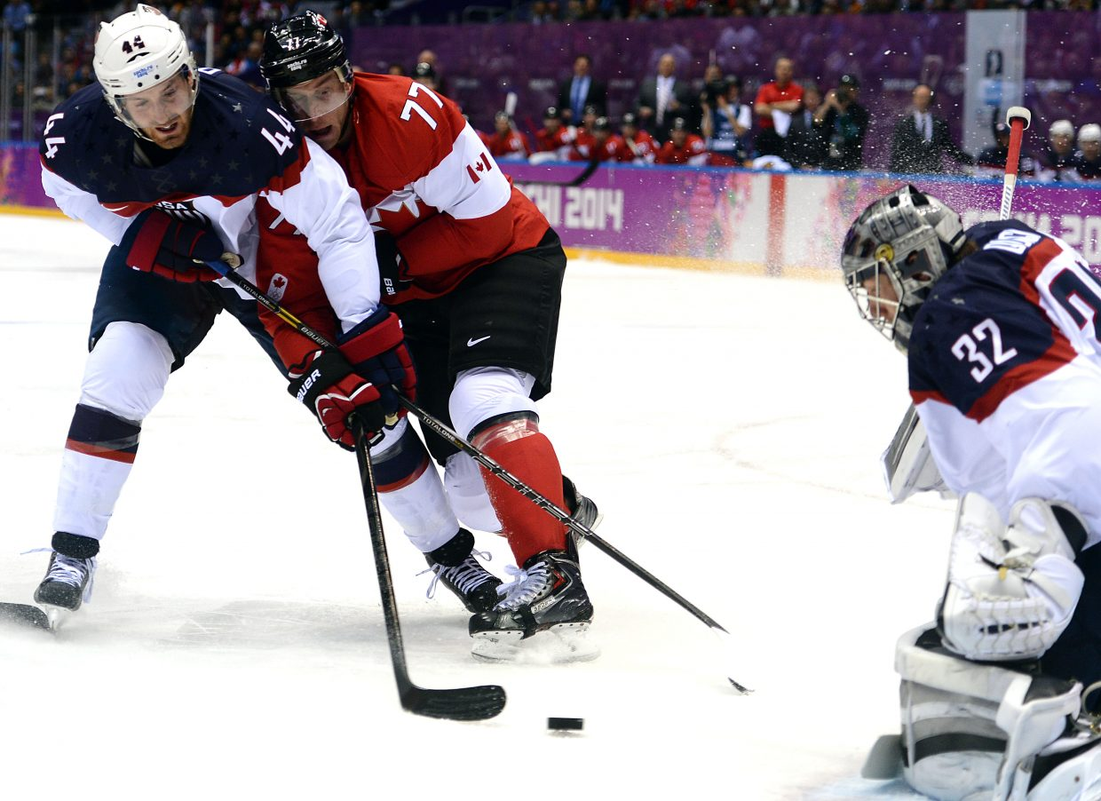 U.S. hockey player Brooks Orpik and Canadian Jeff Carter battle for the puck in front of U.S. goalie Jonathan Quick on Friday during the semifinal game of the men's hockey tournament at the 2014 Winter Olympics.