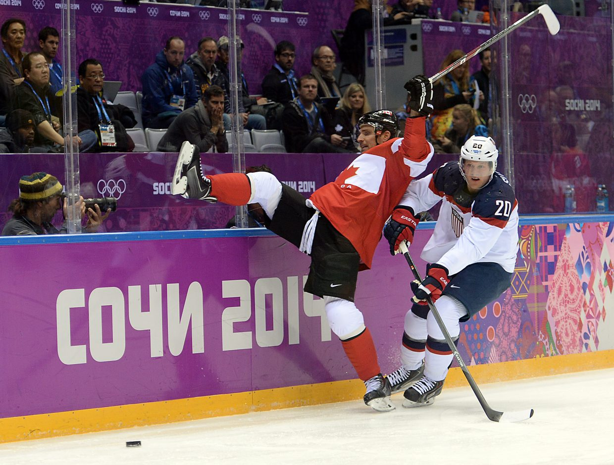 Canada's Patrick Sharp and the United States' Ryan Suter tangle Friday during the semifinals of the men's hockey tournament at the 2014 Winter Olympics.