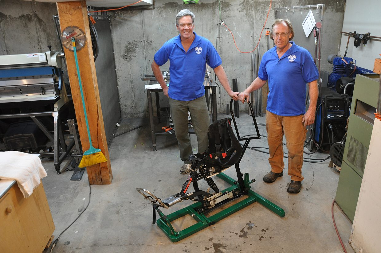 Steve Harrison, left, and Wes Dearborn pose with an early model of their sit ski simulator in Steamboat Springs. The device allows people with disablities to practice sit skiing before they hit the slopes.