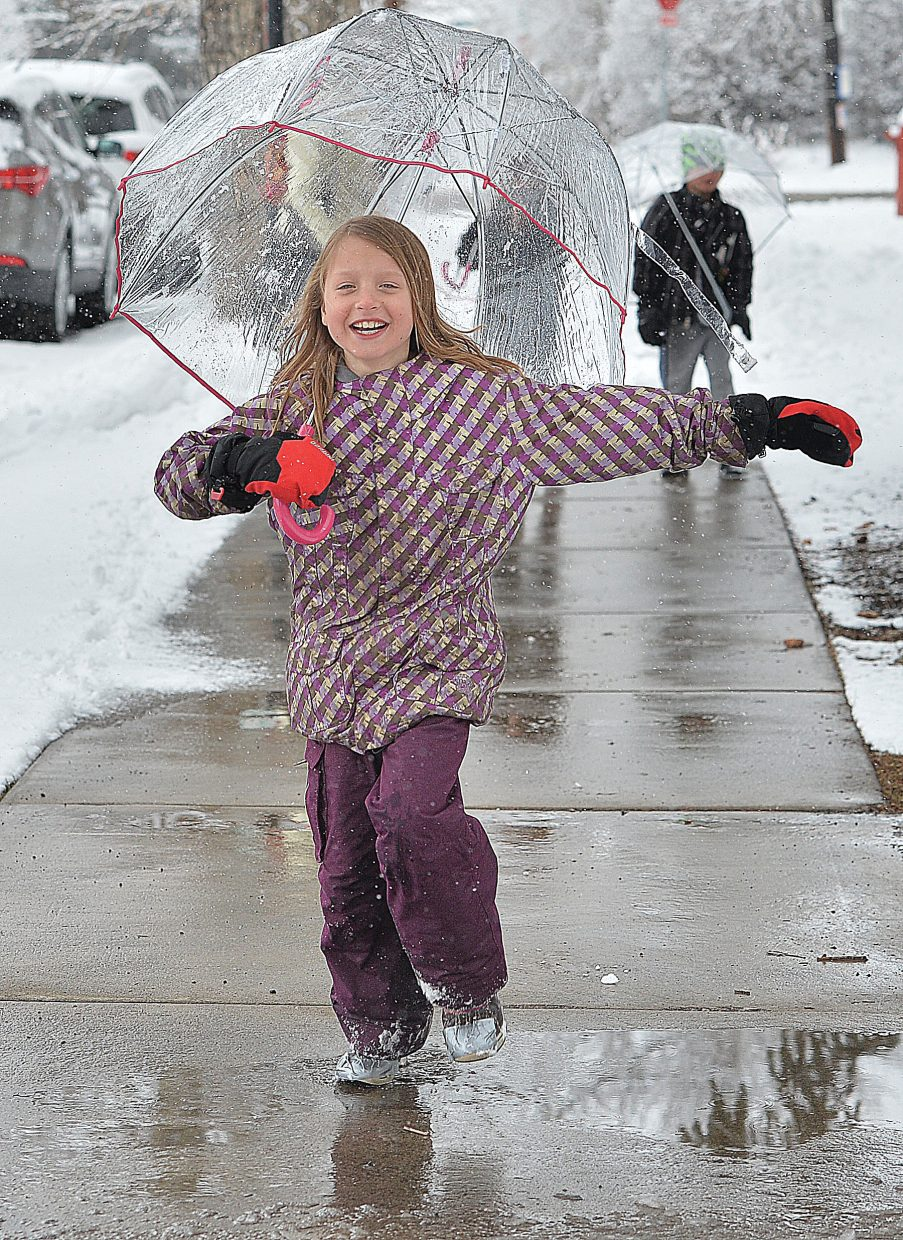 Sophia Picking didn't let Friday's wet, wintery weather stop her from having a good time with her brother, Andrew, and little sister, Izzy. With umbrellas to keep them dry, the children made their way through the puddles and falling snow downtown with the grandma, Adele.