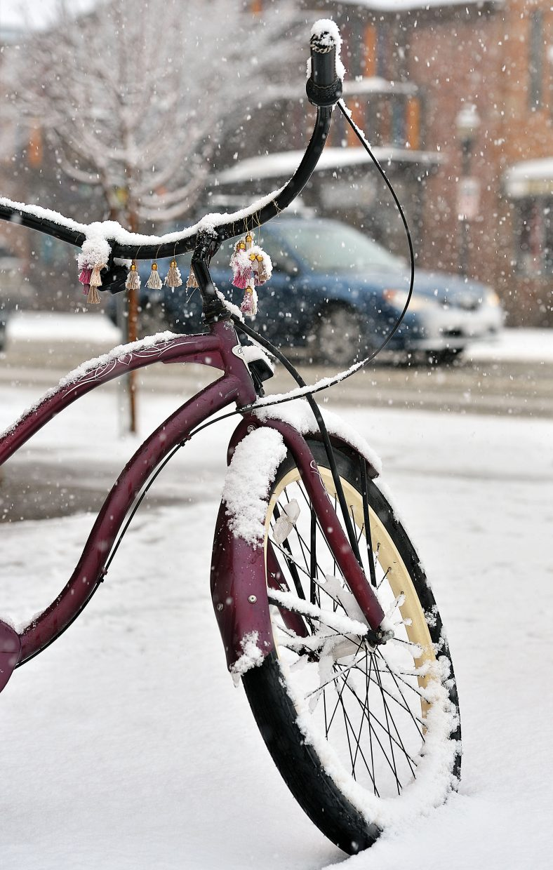 A bike sits covered in snow near the corner of Ninth Street and Lincoln Avenue Friday morning. After several days of spring-like weather residents of Steamboat Springs woke up to more seasonable weather on Friday.
