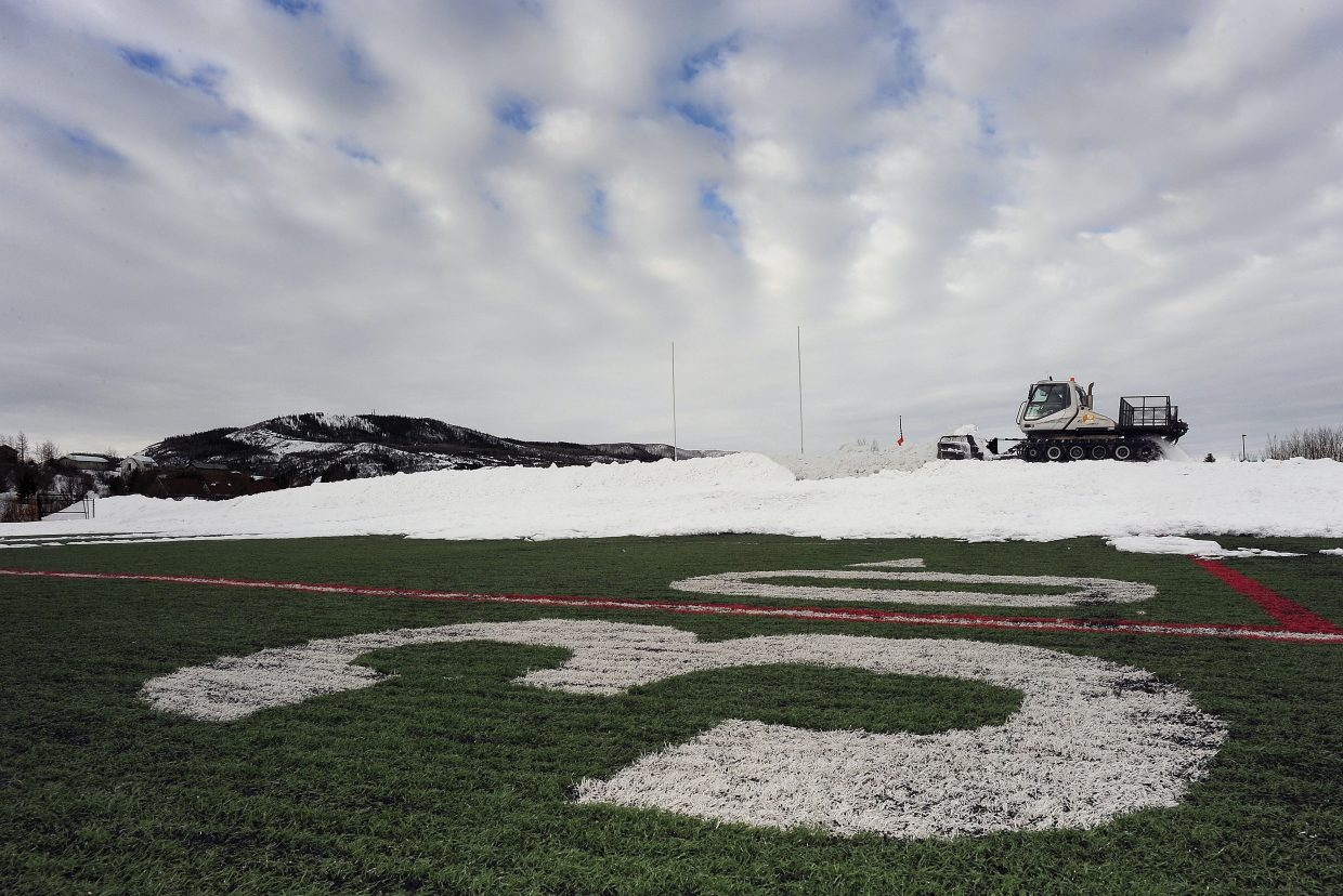 Dennis Johnson, of Native Excavating, uses a snowcat to move snow off the high school football field Monday morning. Native Excavating and Steamboat Ski Area donate equipment and operators to help get the fields ready for the start of the spring season every year. The season officially began Monday, and the field is nearly game ready.