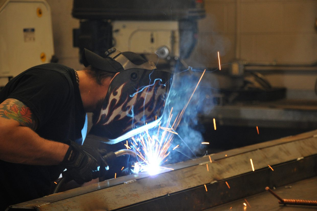 "Levi Wisecup does some welding on a trough that goes into the city's pot hole patching truck. Wisecup says he was ""born to turn wrenches."""
