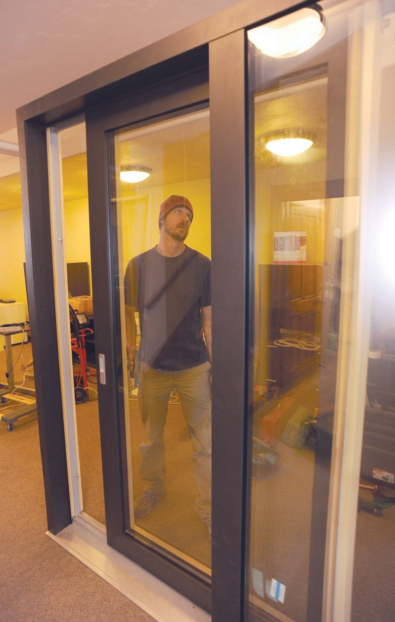 Ethan Smith, a service technician for Zola Windows, checks out an environmentally sound sliding door while installing a display window in the company's new showroom on Hilltop Parkway.