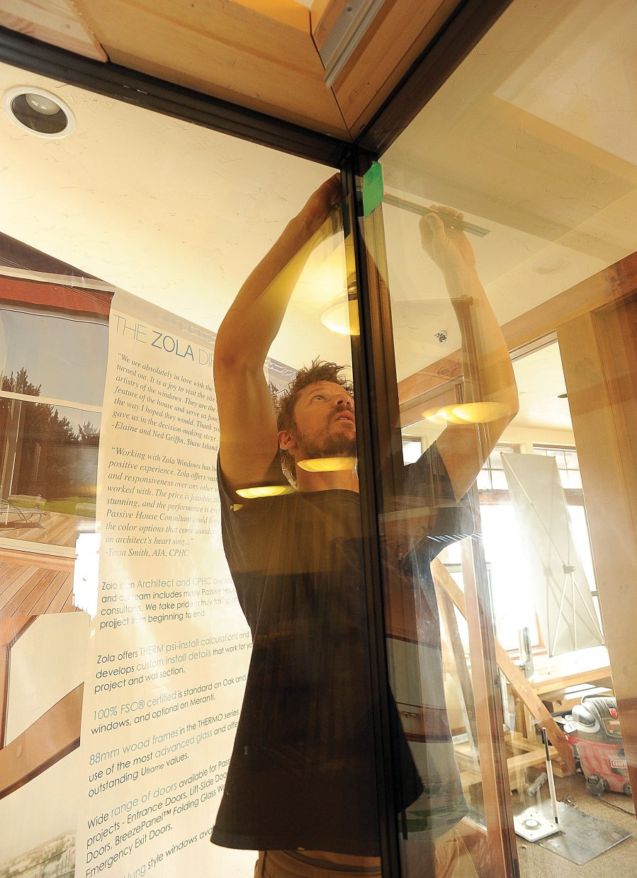 Ethan Smith, a service technician for Zola Windows, installs a display window in the company's new showroom on Hilltop Parkway.