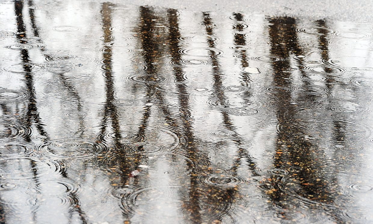 Raindrops fall into a puddle reflecting nearby trees at the base of Howelsen Hill on Thursday afternoon. Warm temperatures and rain helped make the final week of February seem more than a little like spring.