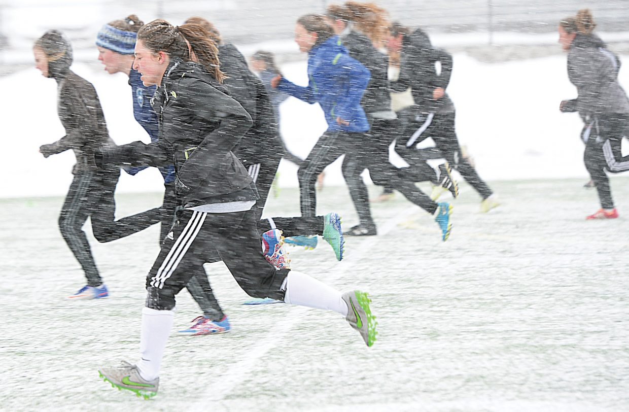Junior Teagan Ludwick runs through the snow at the Steamboat Springs High School athletic field Monday on the first day of spring practice for the girls soccer team. Springs sports, including boys lacrosse, girls lacrosse, track and field, girls soccer, boys baseball, girls tennis and girls golf, kicked off the new season despite the fact that the weather wasn't very springlike.