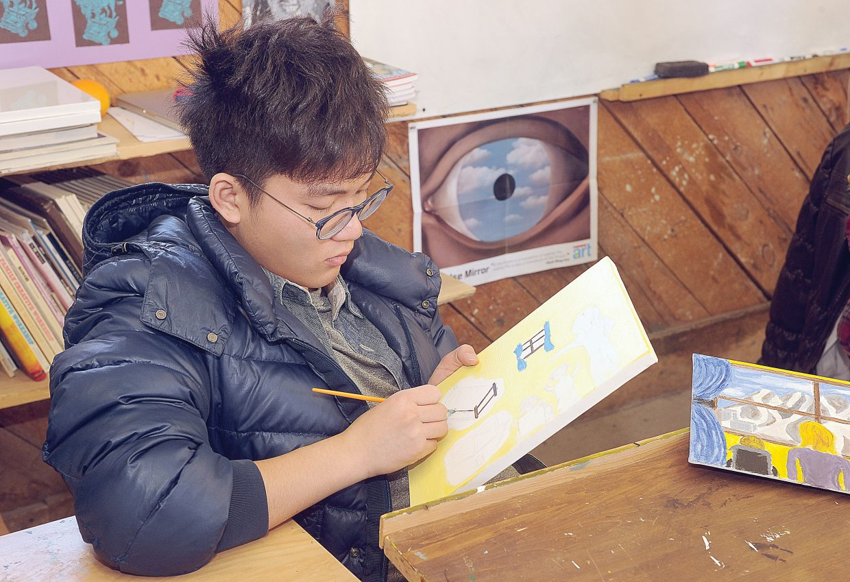 The Lowell Whiteman School student Myron Zhang works on an illustration for a children's book written by Trish Carpenter. Carpenter teamed up with Lowell Whiteman art teacher Claire Gittleman to make illustrating the book part of a class project.