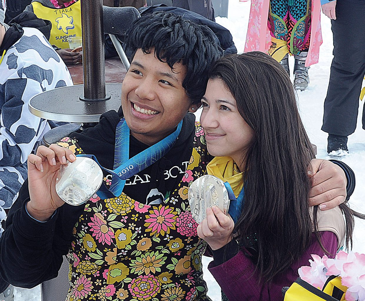 Mitchell Xayapraseuth, or Alaska, and Emily Garcia, of Texas, pose with Johnny Spillane's Olympic silver medals Friday at the Sunshine Kids annual Winter Games at Steamboat Ski Area. The Sunshine Kids is a nonprofit organization dedicated to children with cancer. It provides positive group activities and emotional support for young cancer patients and brings a group to Steamboat Ski Area each year.
