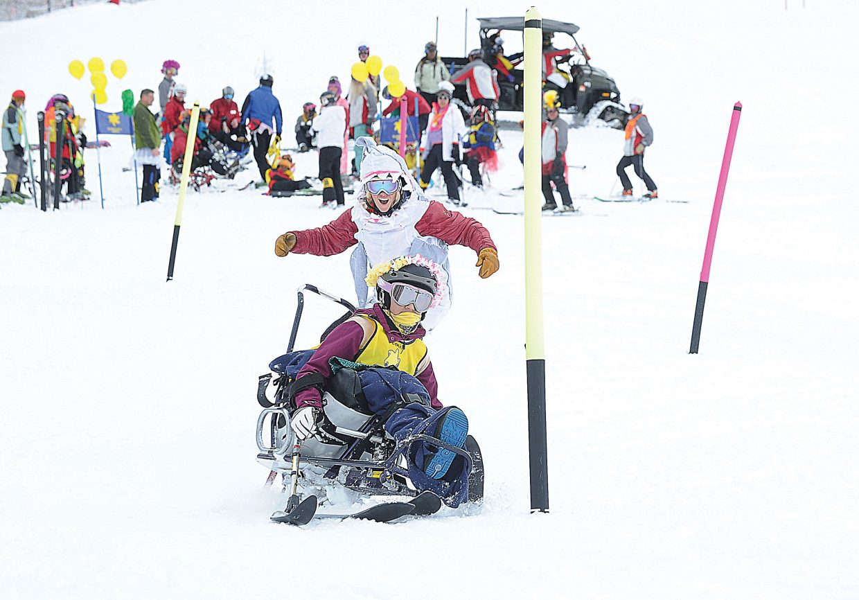 Sunshine Kids participant Emily Garcia, of Texas, and STARS coach Cheyna Swartz race down the Bashor ski run during the annual Sunshine Kids Winter Games at Steamboat Ski Area. The Sunshine Kids is a nonprofit organization dedicated to children with cancer. It provides positive group activities and emotional support for young cancer patients, and brings a group to the Steamboat Ski Area each year.