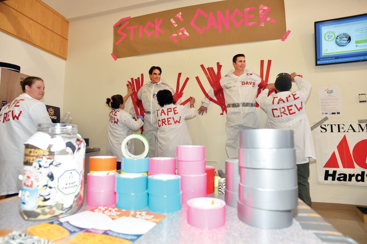"""Members of the """"Tape Crew"""" use duct tape to hold Yampa Valley Medical Center CEO Frank May, left, and COO Dave Garner to the wall inside the hospital's cafeteria. The event was a fundraiser for the upcoming Penguin Plunge, which will be held at noon March 21 at the Catamount Lake House pool."""