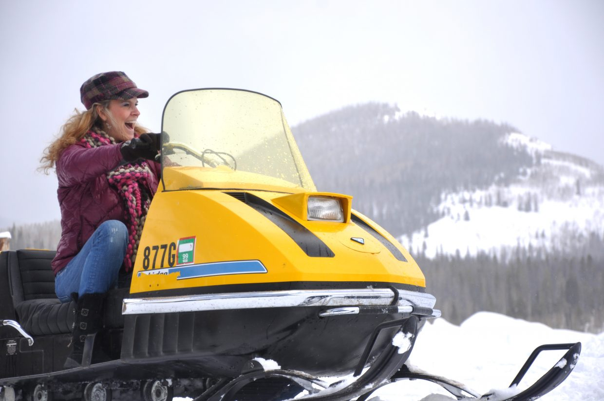 Angie Chatham goes for a ride on a vintage snowmobile at Hahn's Peak Roadhouse. The first vintage snowmobile rally featured several sleds from the 1970s and 1980s.