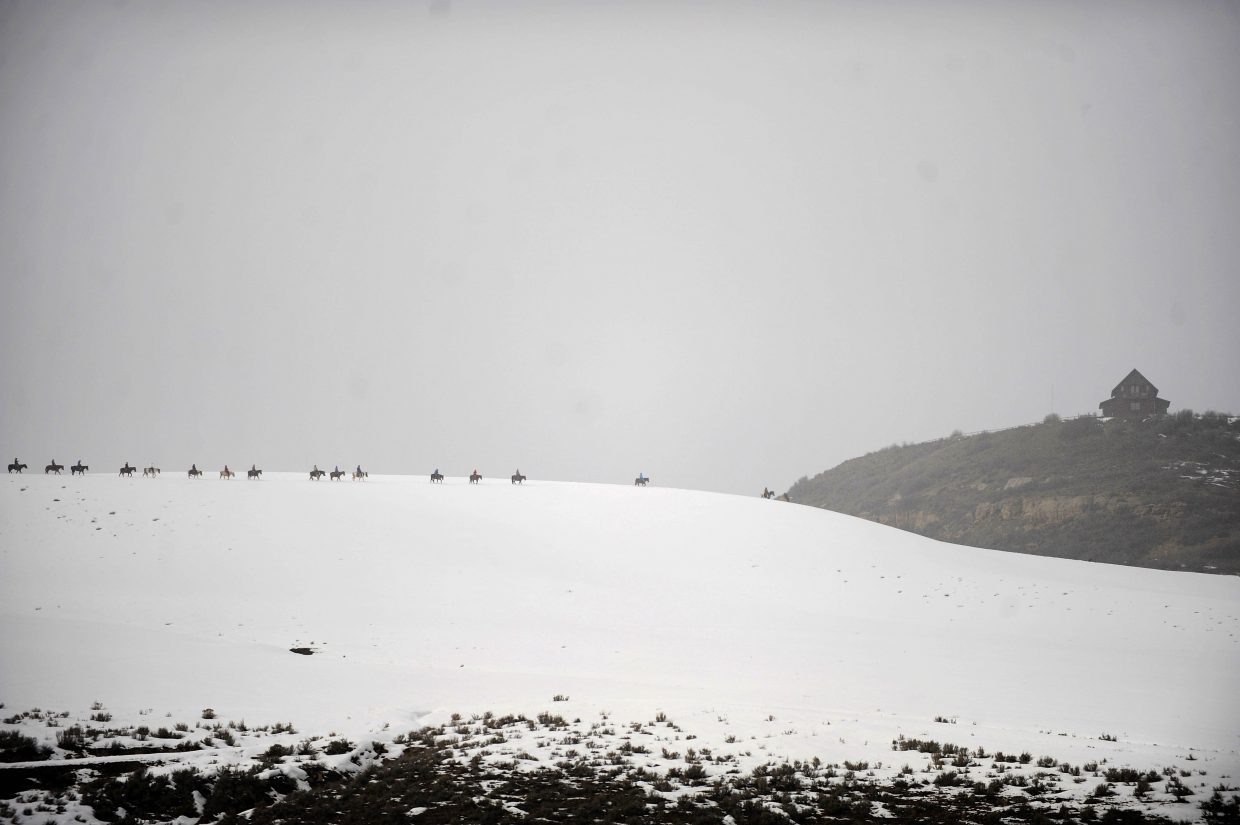 Horses are ridden over a snowy ridge at Saddleback Ranch.