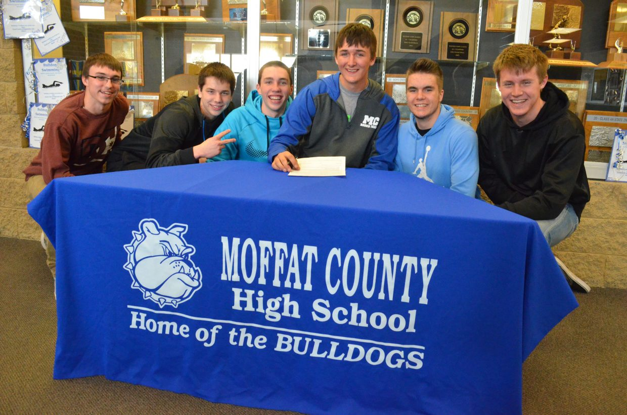 Moffat County High School senior Dusty Taylor, center, seated, is joined by friends and fellow Bulldog athletes, from left, Blake Ludgate, Scott Foster, Dylan Kincade, Ben Robinson and Connor Knez as he prepares to sign his letter of intent to join the University of Wyoming rodeo team. Taylor also played varsity basketball for MCHS.