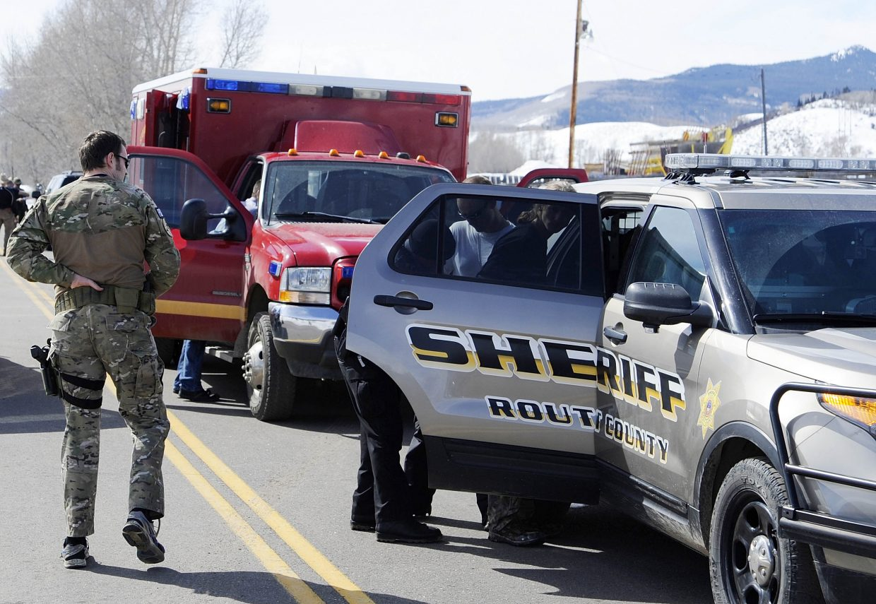 Routt County Sheriff's Office deputies take one of the three juvenile carjacking suspects into custody near Yampa Friday.