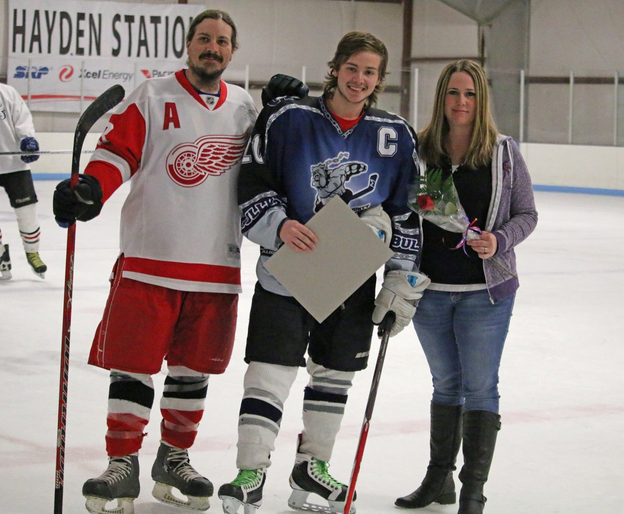 Moffat County High School senior Brodey Gutierrez, center, is joined by his parents before the Bulldogs' final weekend at Moffat County Ice Arena. Gutierrez served as a team captain and was the lone senior this season.