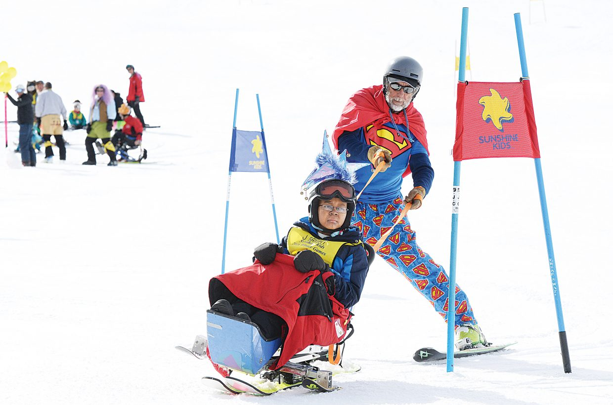 Sunshine Kid Johnny Bright, age 14, from Sterling, VA makes his way down the racecourse with STARS volunteer Dave Estey Friday afternoon at the Bashor Bowl Friday afternoon. Bright was one of 25 children who spent the week at Steamboat Ski Area as part of the annual Sunshine Kids Foundation skiing event.