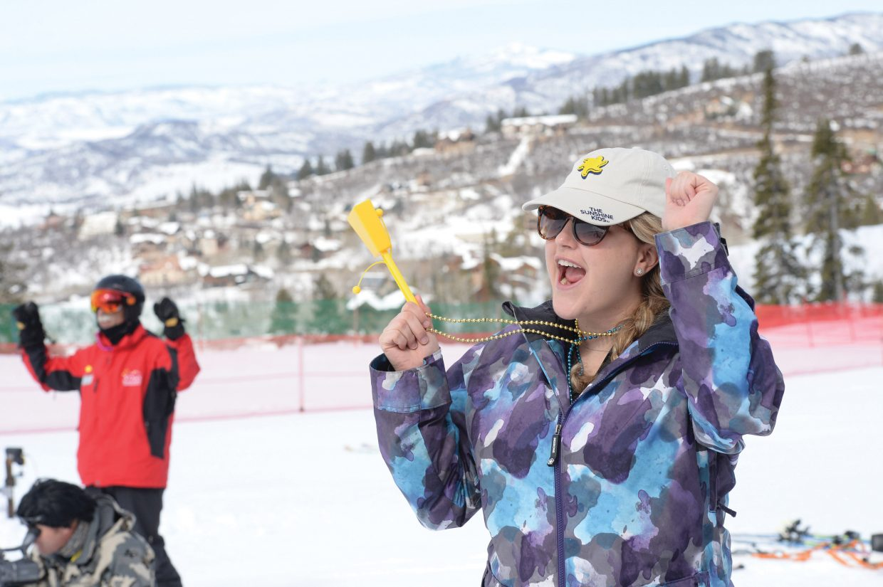 Sunshine Kids volunteer nurse Jackie Becker, an R.N. from Children's Hospital of Colorado, cheers on the field in this year's race, which was held at the base of the Bashor Bowl Friday.