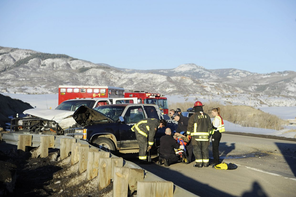 Emergency responders help a patient involved in a two-car crash Friday evening at Routt County Road 42 and U.S. highway 40. No life-threatening injuries were reported.