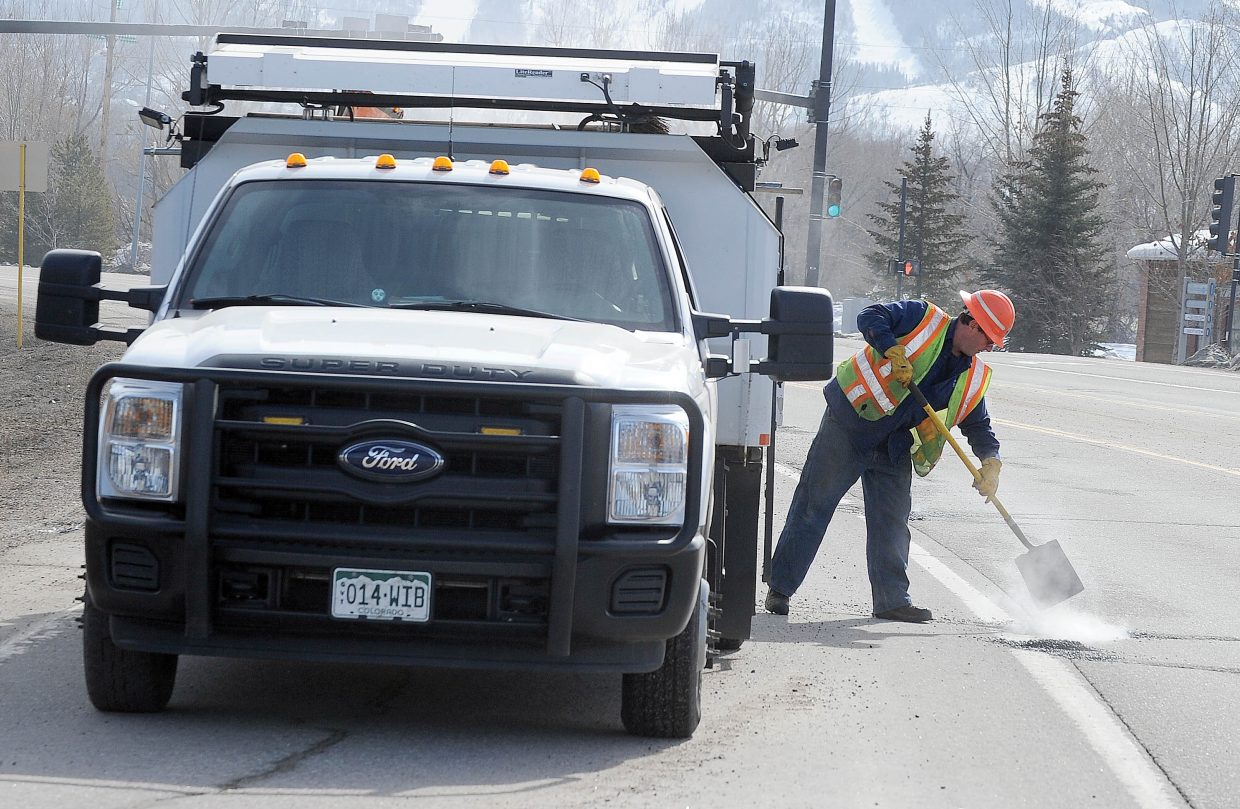 """Colorado Department of Transportation employee Dan O'Connor uses a """"cold mix"""" to fill potholes along U.S. Highway 40 near the Stockbridge Transit Center in Steamboat Springs."""