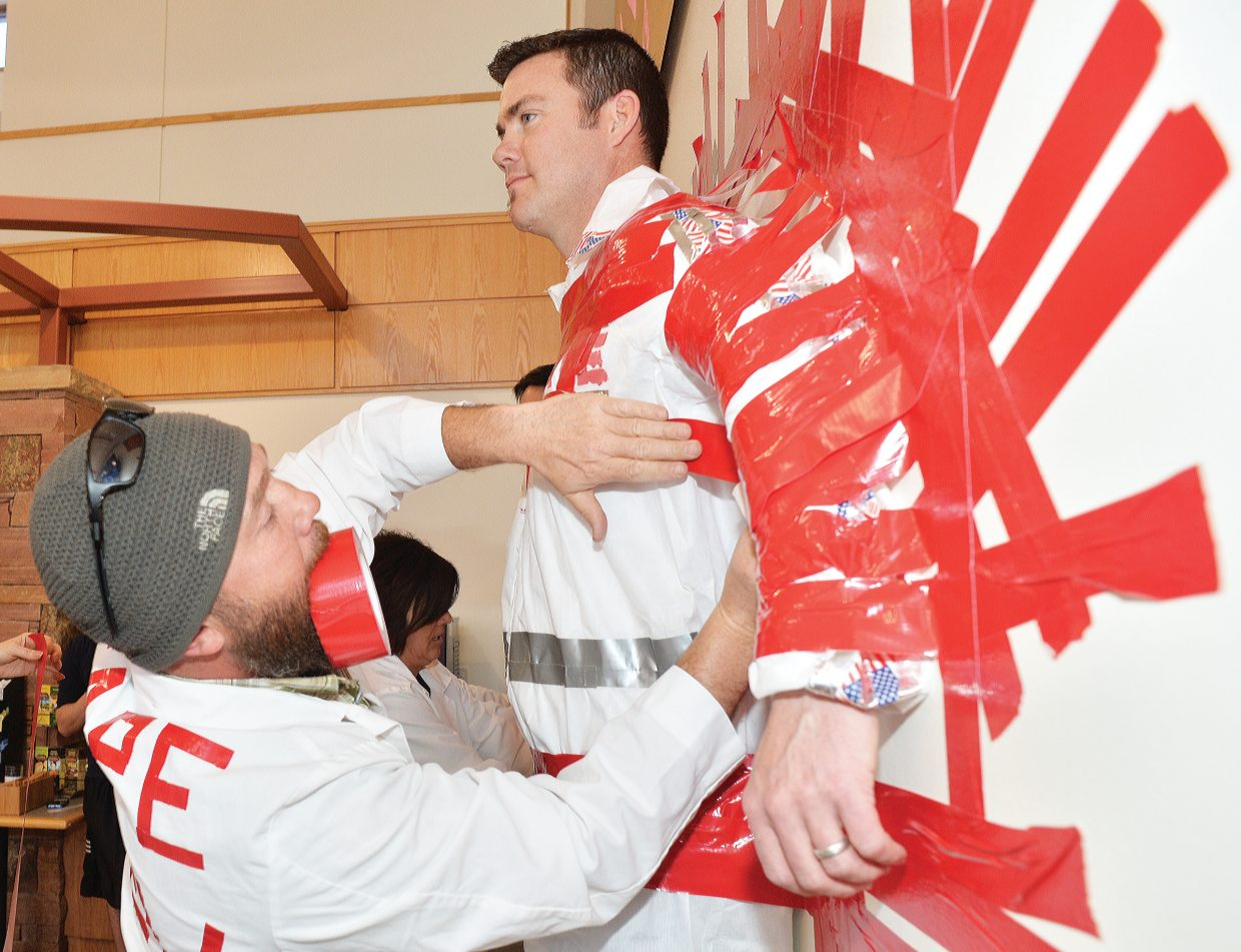 """Tape Crew member Jim Fletcher duct tapes Yampa Valley Medical Center COO Dave Garner to the wall inside the cafeteria as part of """"Stick It To Cancer."""" The event was a fundraiser for this year's Penguin Plunge."""