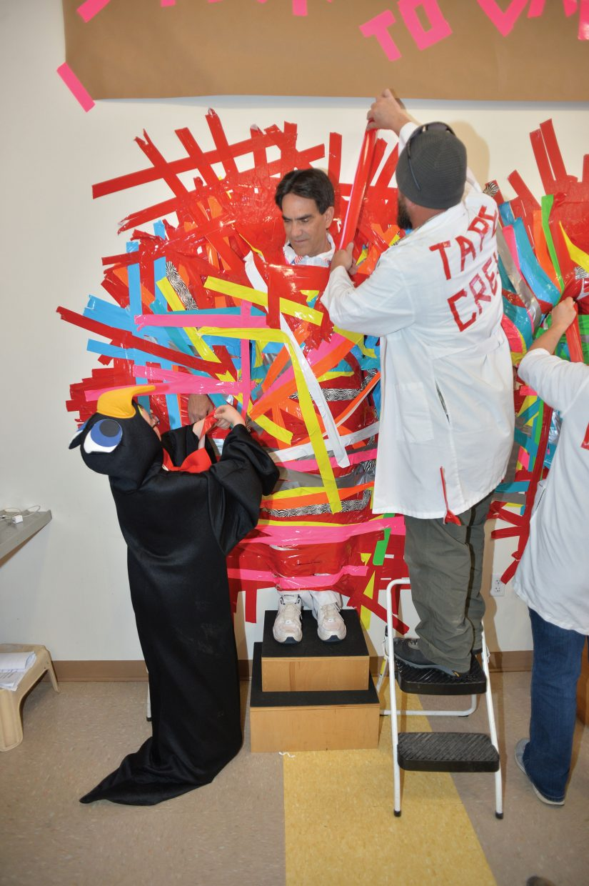 "Tape crew member Jim Fletcher and his assistant Levi Wofford (the penguin) duct tape Yampa Valley Medical Center CEO Frank May to the wall inside the cafeteria as part of ""Stick It To Cancer."" The event was a fundraiser for this year's Penguin Plunge."