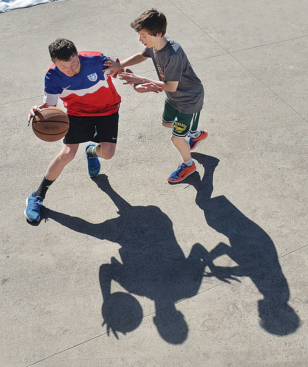 Cole Puckett attempts to get past his brother Cooper in a game of one-on-one basketball in the family's driveway Friday morning. There was no school Friday as teachers took part in a professional development day.