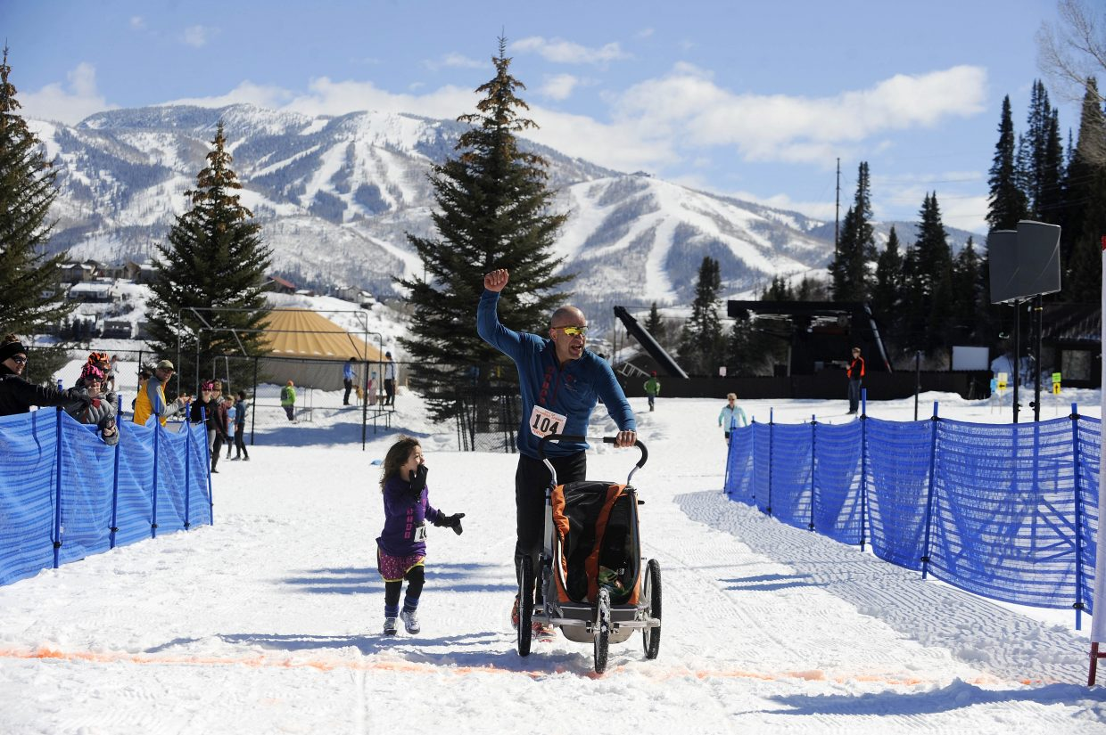 Graham Muir crosses the finish line with his daughter Zoe during the 23rd annual Steamboat Pentathlon on Saturday at Howelsen Hill.