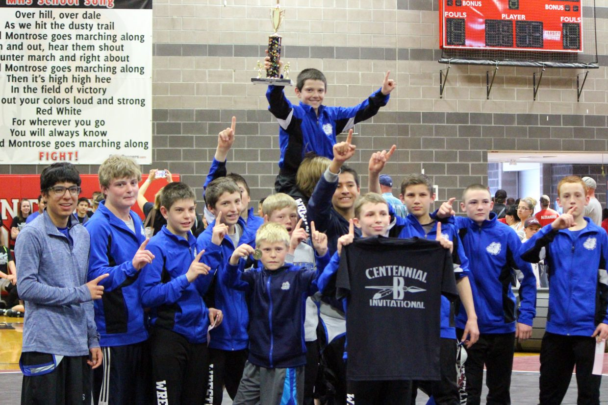 The Craig Middle School varsity wrestling team lifts high their honors as the top squad of the Centennial Braves Invitational Saturday in Montrose.