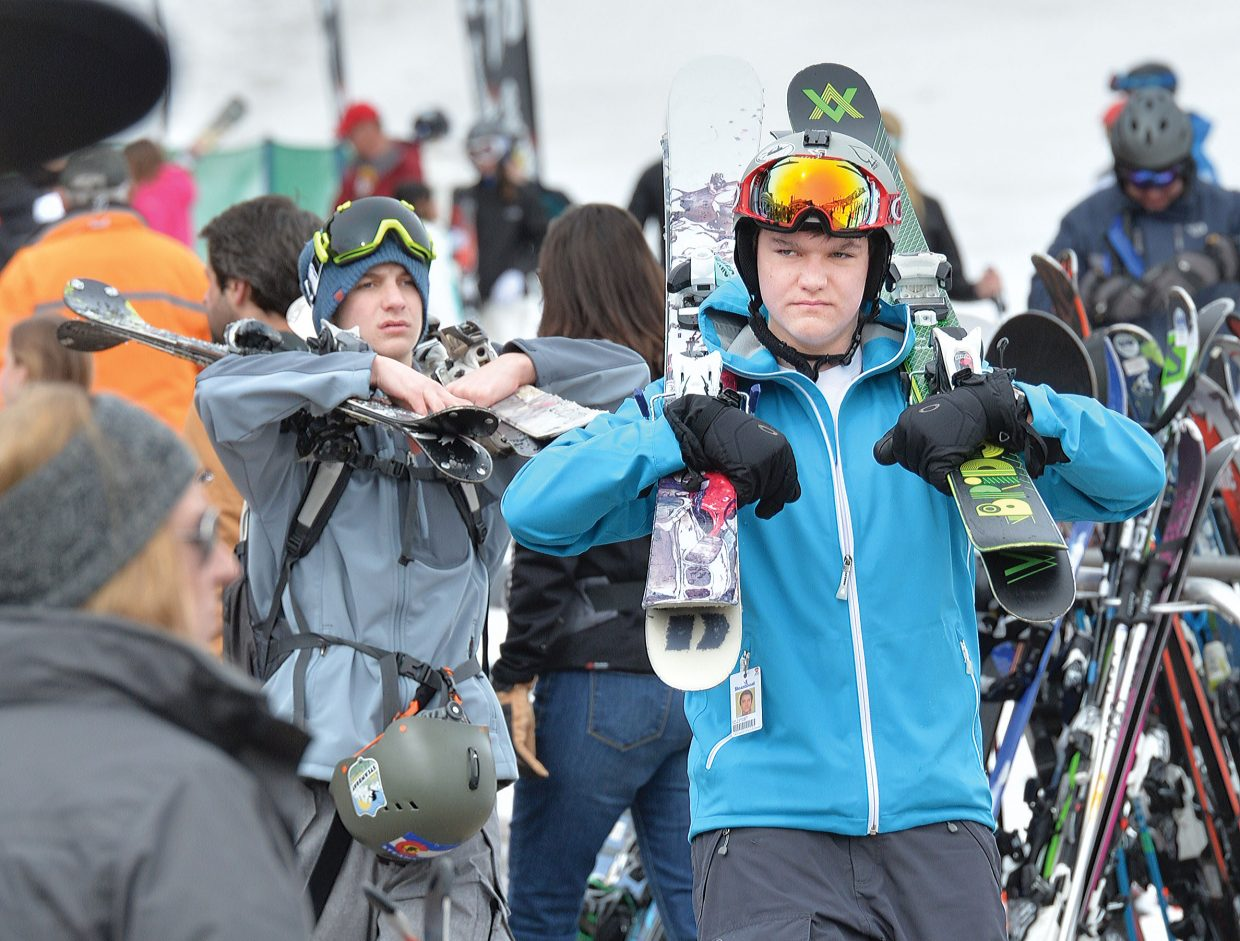 Sam Zummach and his brother Josh had their hands full with skis Thursday afternoon as they made their way through the crowd at the base area of Steamboat Ski Area. Despite an overcast sky, skiers enjoyed spring-like conditions. Over 13,000 visitors are expected in town Saturday.