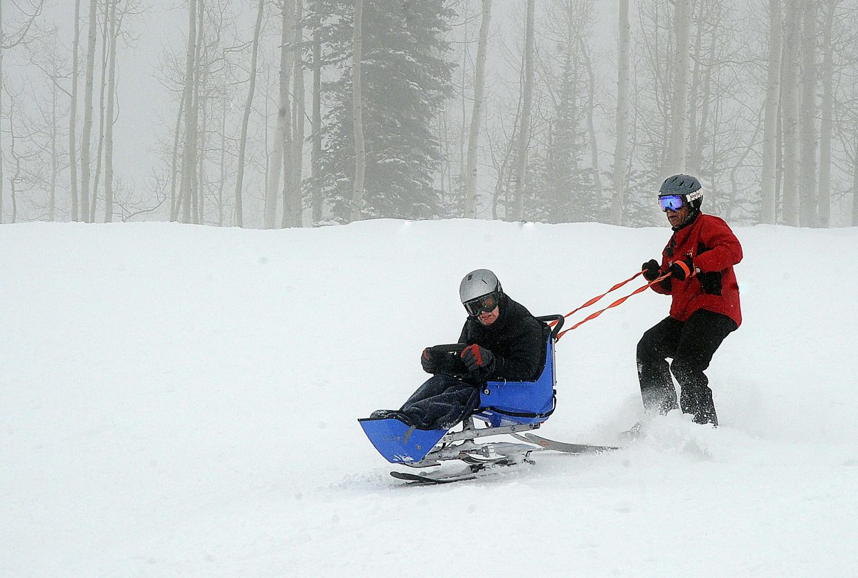 Jim Cartwright skis down Vagabond at the Steamboat SKi Area on Monday morning with Steamboat Adaptive Recreational Sports Operations Director Ron Southworth.