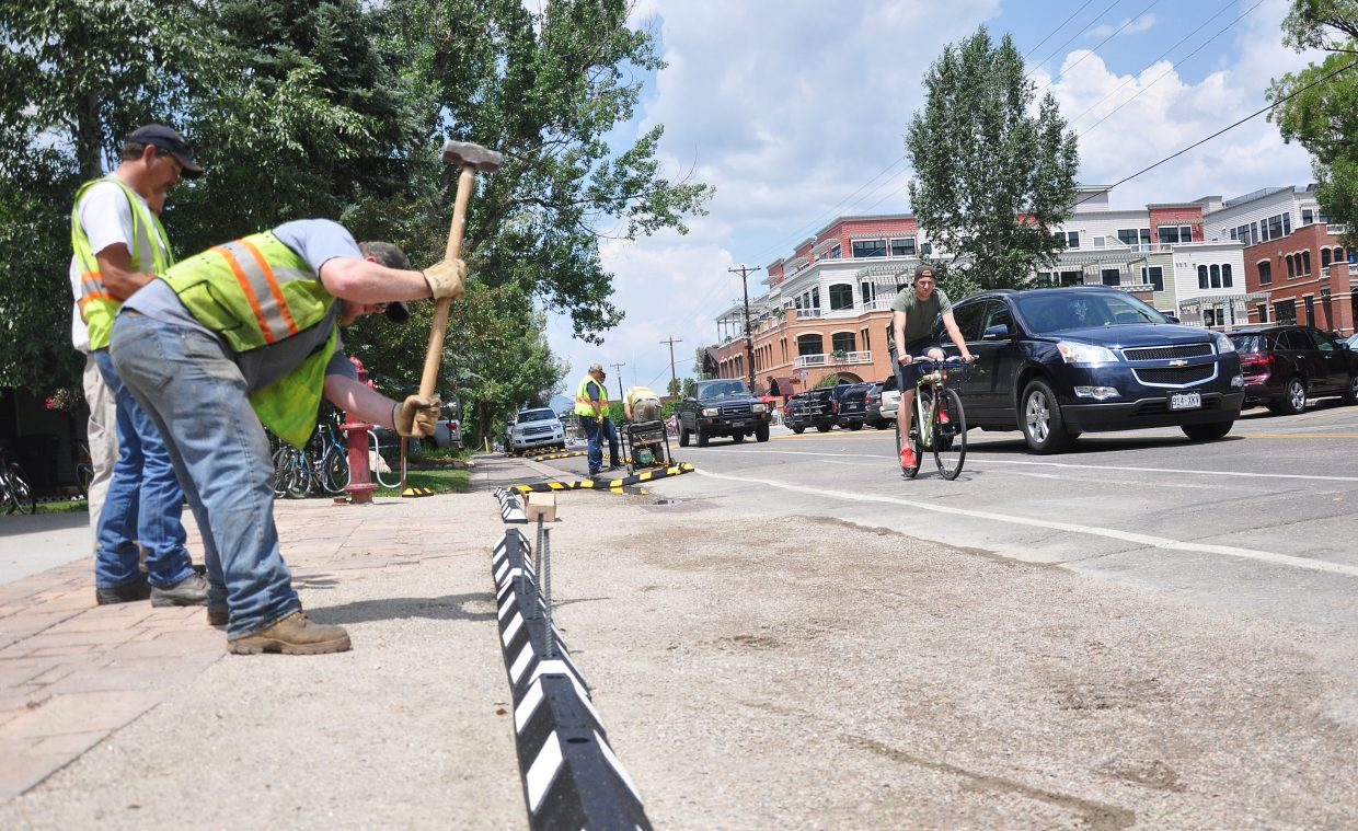 City employees hammer down temporary curb stops on Yampa Street in 2014. A downtown investment plan proposed by the city would install permanent curbs on the busy downtown roadway.
