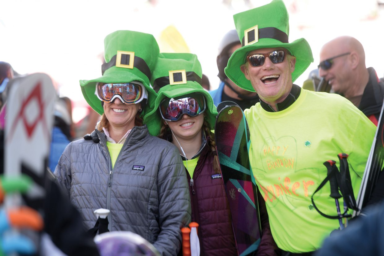 Skiers Jennifer, Drew and Scott Bergquist show their St. Patrick's Day spirit Friday morning as they wait in line to ride the gondola up the slopes of the Steamboat Ski Area.
