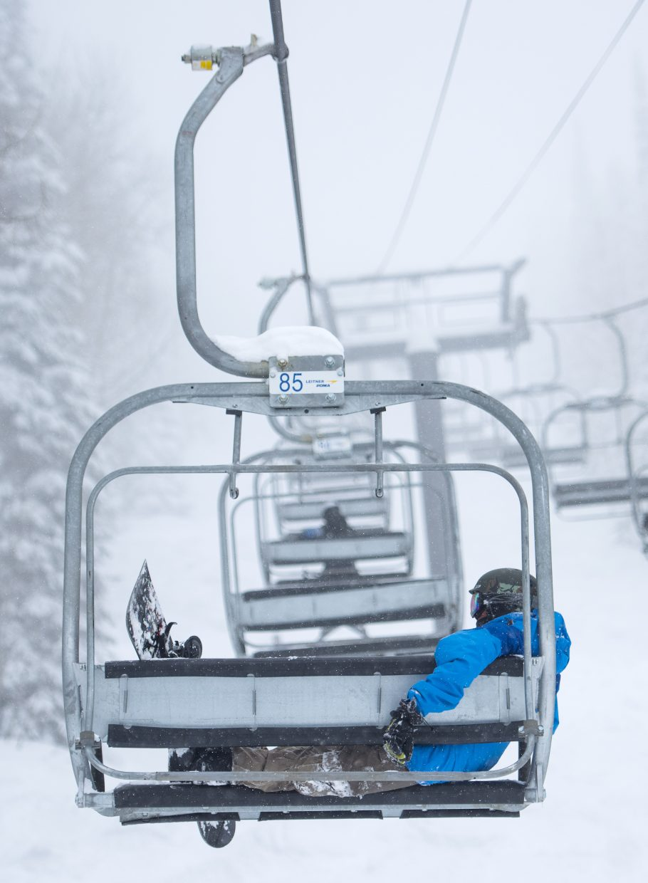 Snowboarder Brandon Roberts, in Steamboat Springs from Fort Collins, takes a moment to relax while riding the Burgess Creek chairlift on Thursday at Steamboat Ski Area.