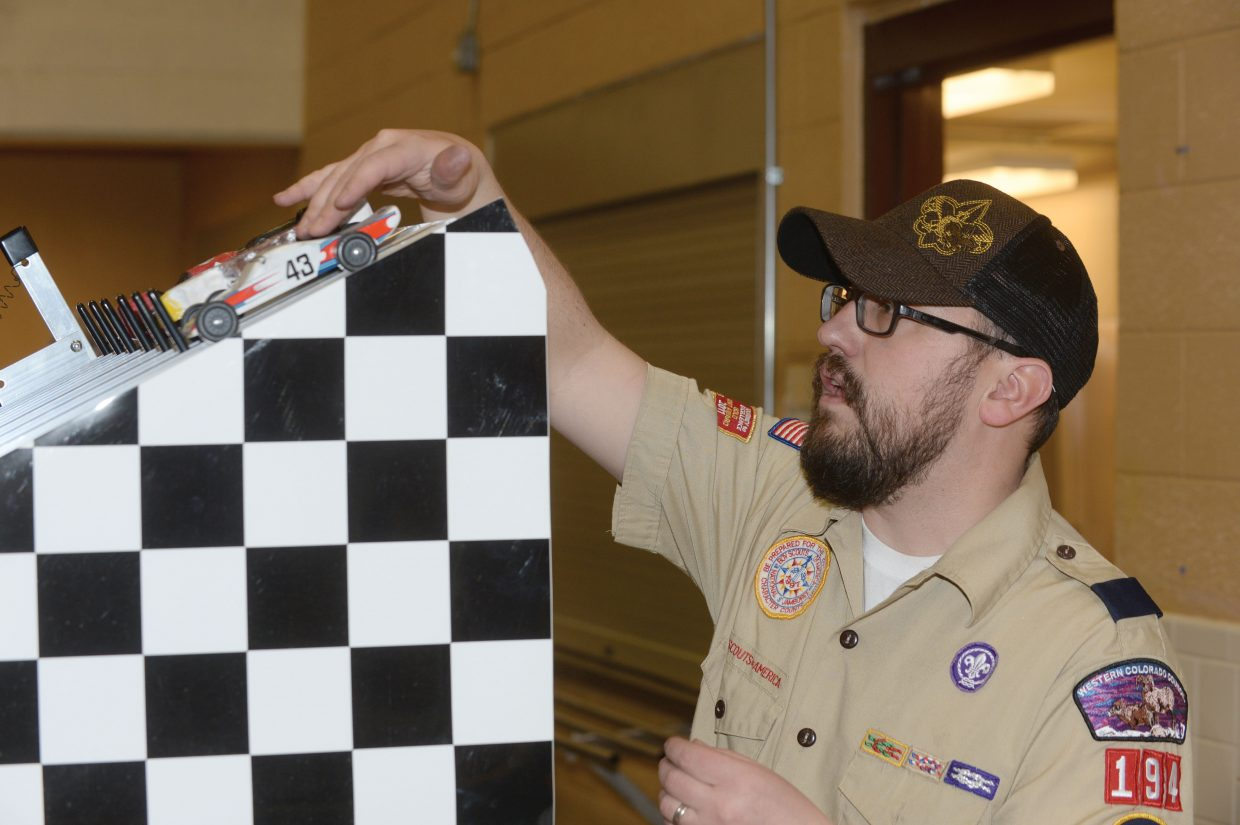 Cub Scout leader Bradley Moline sets Pinewood Derby cars into track slots before one of the many races Wednesday at Troop 194's annual Pinewood Derby.