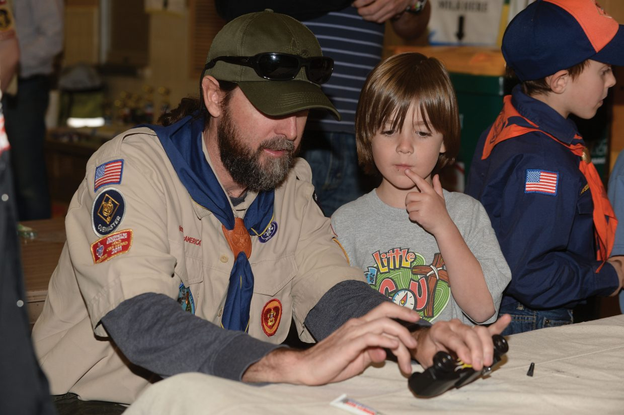 Cub Scout leader Dave Ince helps his son Henry apply graphite to the wheels of his Pinewood Derby car before the race started Wednesday evening at Steamboat Springs Middle School. Steamboat Cub Scout Troop 194 gathers every year to host the races for the local scouts.