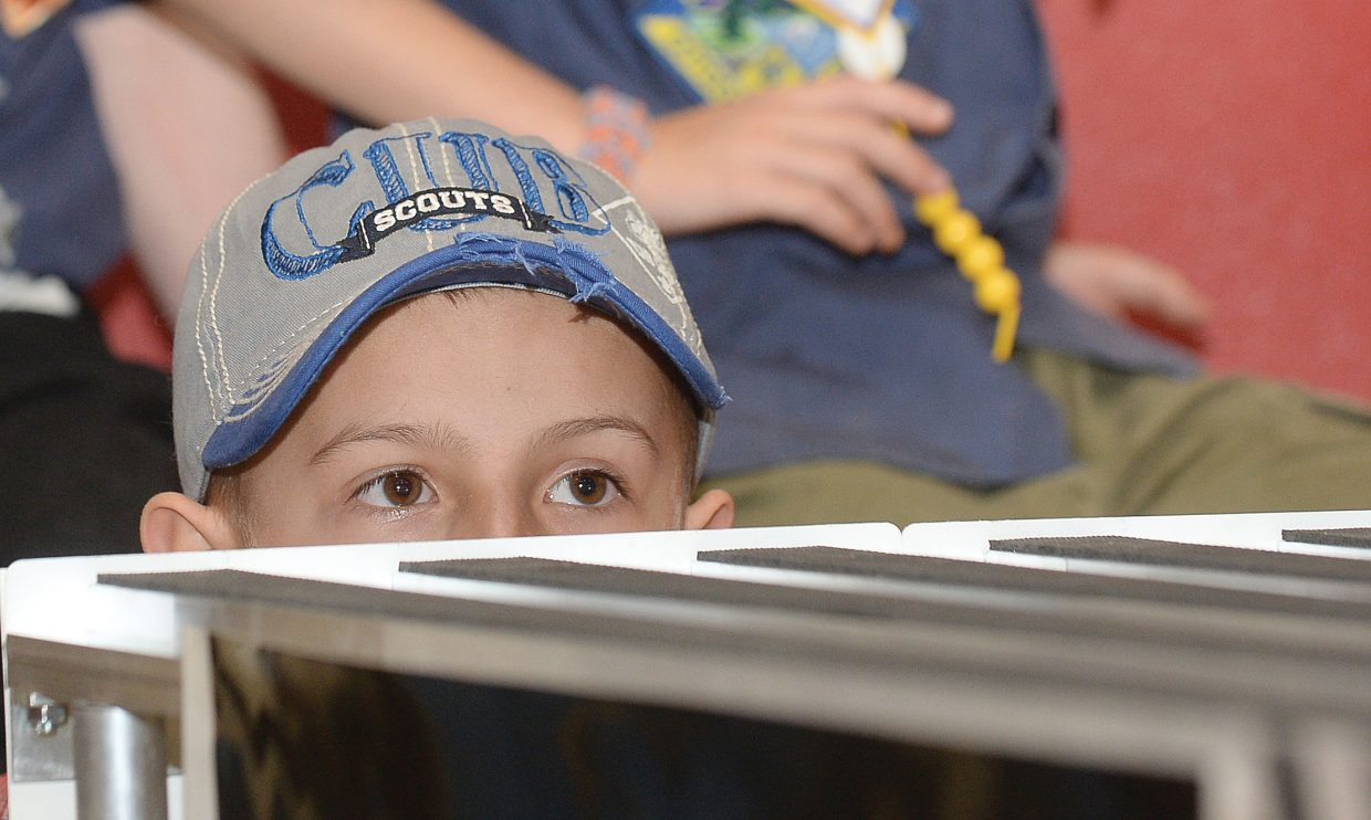 Cub Scout Parker Moline gets at a low angle to watch cars race down the track during the Pinewood Derby on Wednesday evening at Steamboat Springs Middle School. Troop 194 gathers every year to host the races for local scouts.