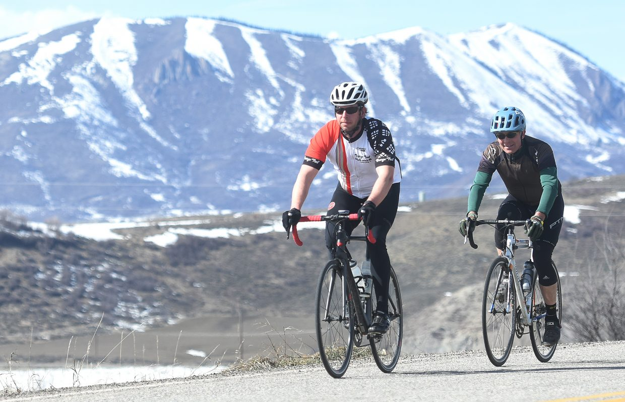Jeffrey Campbell, left, and Chris Lafrenaye stretch their legs with a Saturday afternoon bike ride on Routt County Road 33. Temperatures that punched into the 60s had many around the area out and about as if it were middle of June.