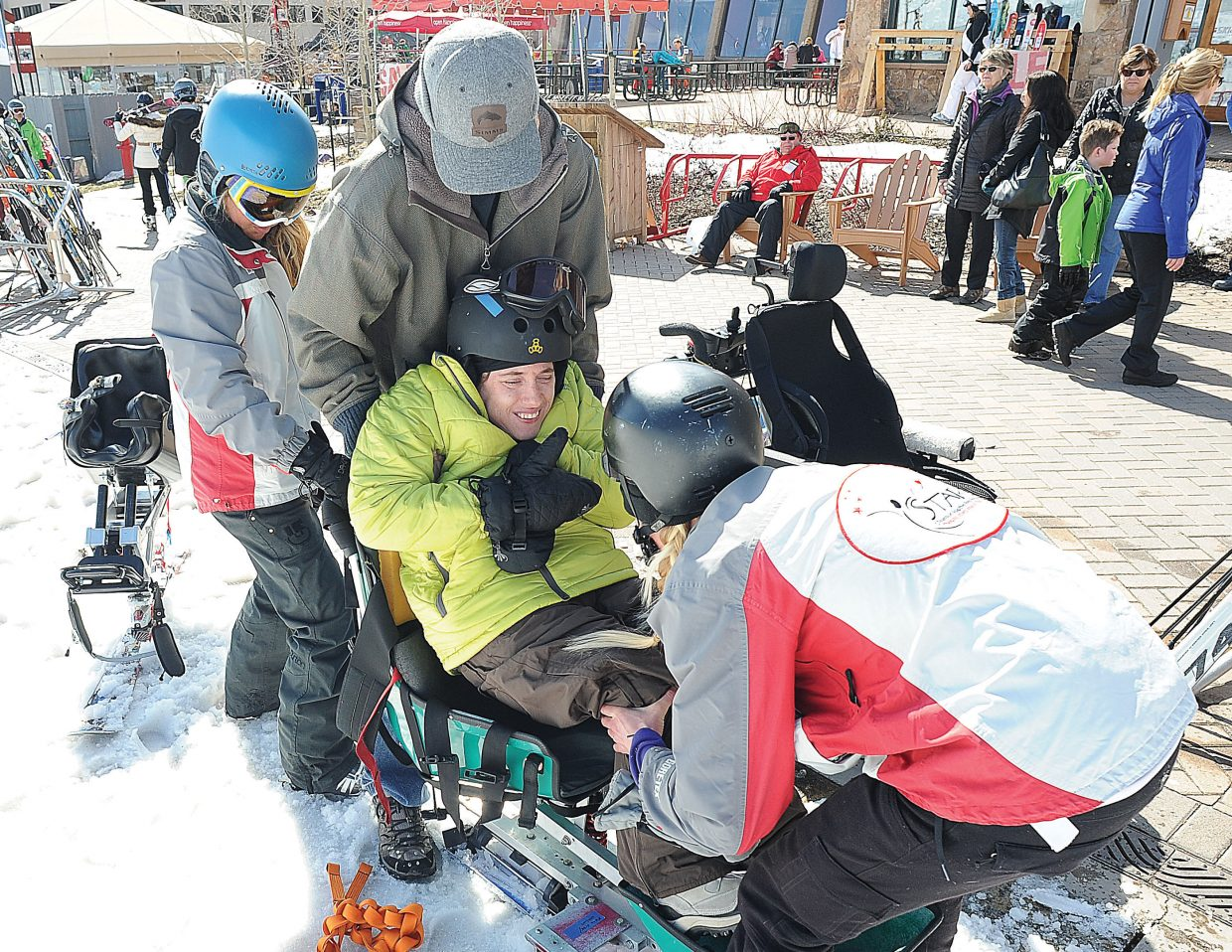 STARS guides Cheyna Swartz (right) and Carly Koczera (left) help Horizons client Alyessa Yeagher into a sit-ski earlier this winter at Steamboat Ski Area. Horizons and STARS have teamed up to offer clients the chance to get on the mountain and ski in the winter.