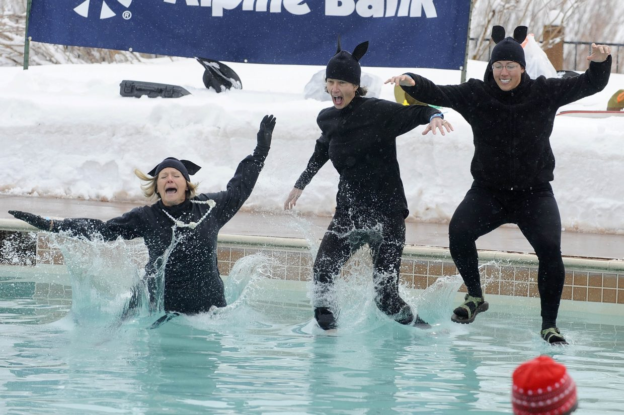 Team Spirit members, from left, Mary Gills, Carol Sitlington and Laura Tomcek jump into the frigid waters at the Lake Catamount clubhouse Saturday during the annual Penguin Plunge fundraiser put on for the Healthcare Foundation for the Yampa Valley. The event raised $85,000 for a planned breast health center at Yampa Valley Medical Center.