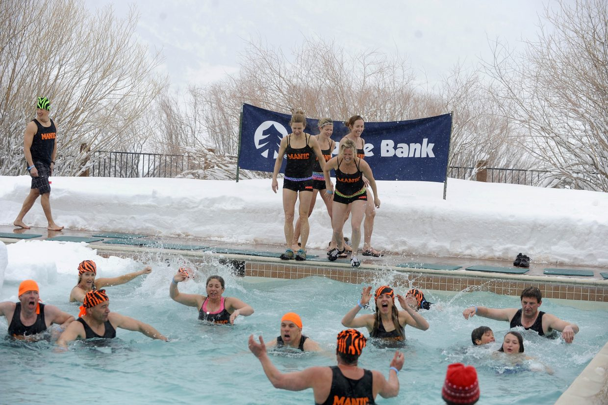 Members of the Manic Training team jump into the frigid waters at Lake Catamount during the Penguin Plunge. About 90 people on 15 teams participated in the event.