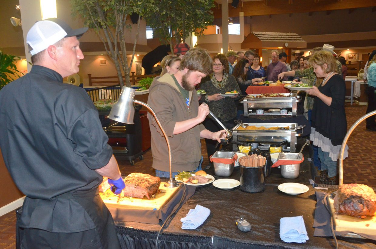 Patrons fill their plates at the buffet during the Safari Club International Yampa Valley Chapter fundraiser banquet Saturday night at the Clarion Inn & Suites.