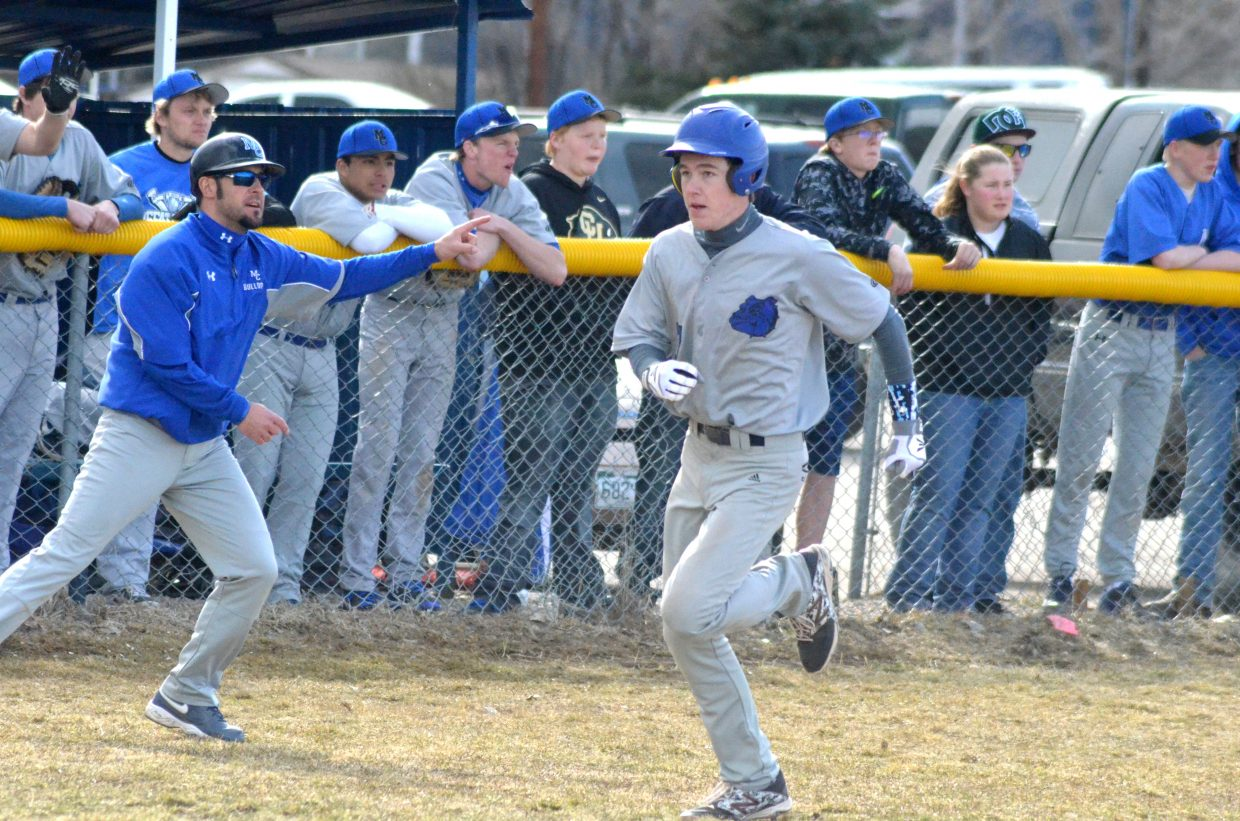 Coach Justin Folley gives base runners the all-clear as Moffat County High School's Spencer Turner rounds third early in the Bulldogs' Tuesday game against Steamboat Springs.