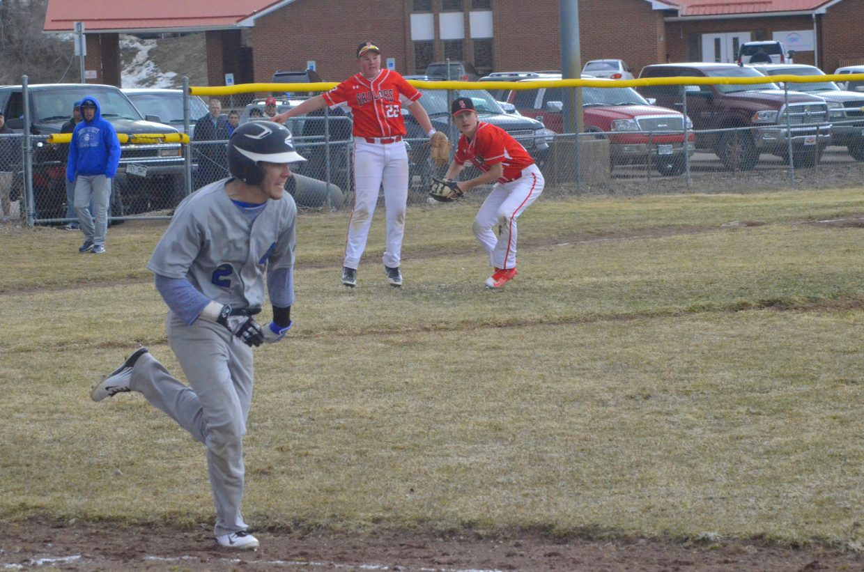 Moffat County High School's Hunter Roberts hustles to first base as Steamboat Springs pitcher Nate Roach scrambles to throw him out after being caught off-guard by a bunt.