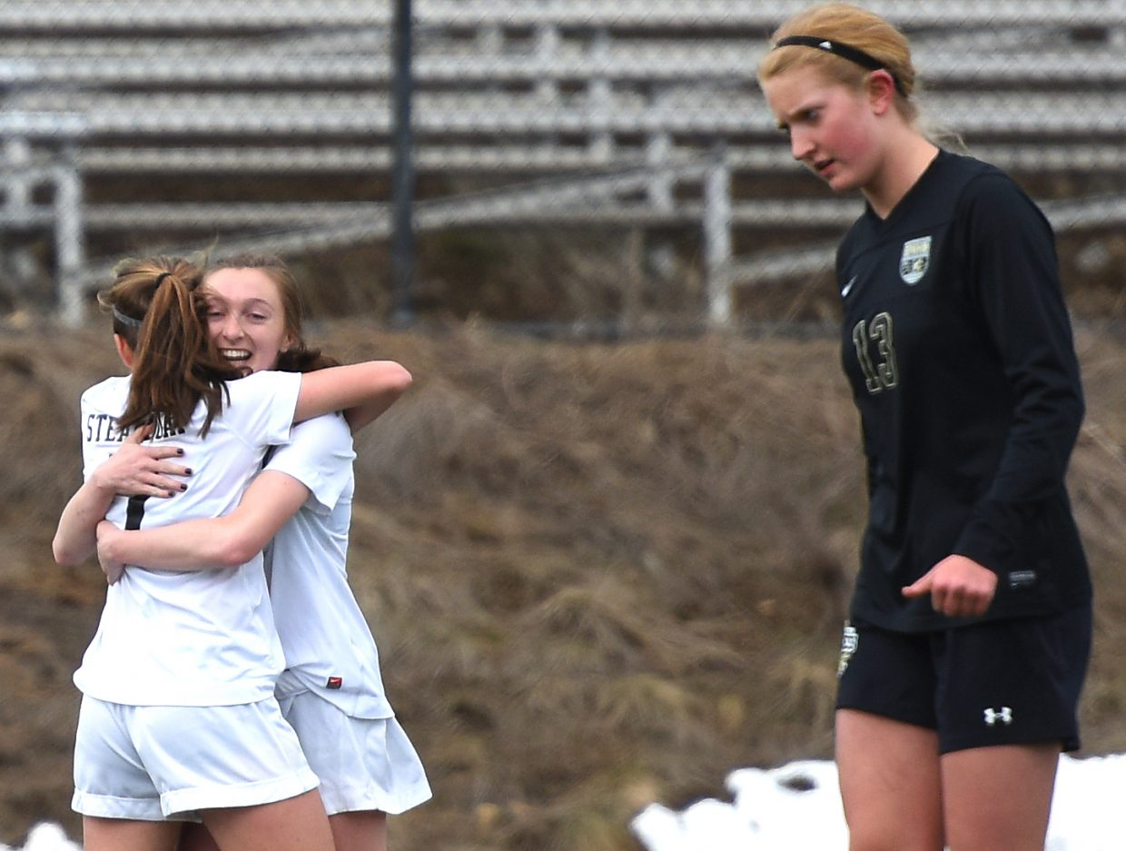 Steamboat's Keelan Vargas, left, and Mackenzie Gansmann hug after Gansmann scored a goal in the first half of Tuesday's game against Battle Mountain.