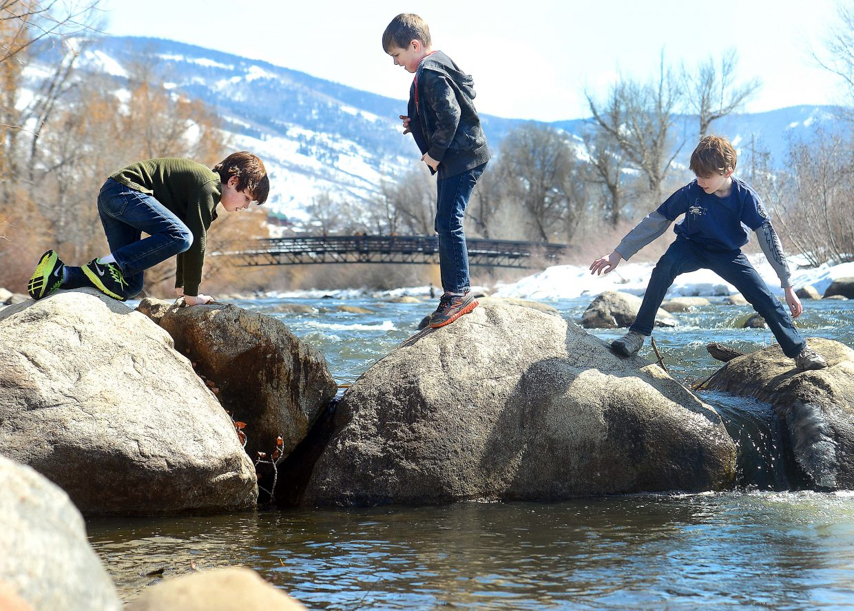 The Paulus brothers — Bobby, 10, left, Davey, 8, and Nick, 11 — play on rocks in the Yampa River on Sunday in downtown Steamboat Springs. The Paulus family arrived in Steamboat from Chicago on Sunday, and their first stop was Yampa Street to stretch their legs. A week of spring break vacation awaits.