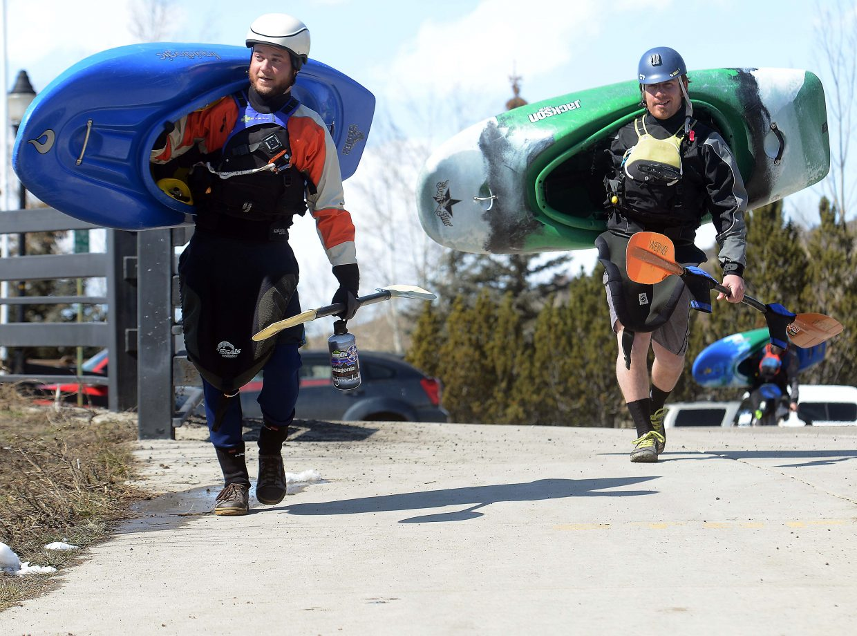 Casey Durbin, left, and Daniel Stadtler head for the Yampa River for some early spring kayaking Sunday in Steamboat Springs. They were joined in the cold river by Kevin Marsh. A month of warm weather was interrupted by snow Saturday, but the sun was back and people were out and about running, walking, biking and kayaking Sunday.