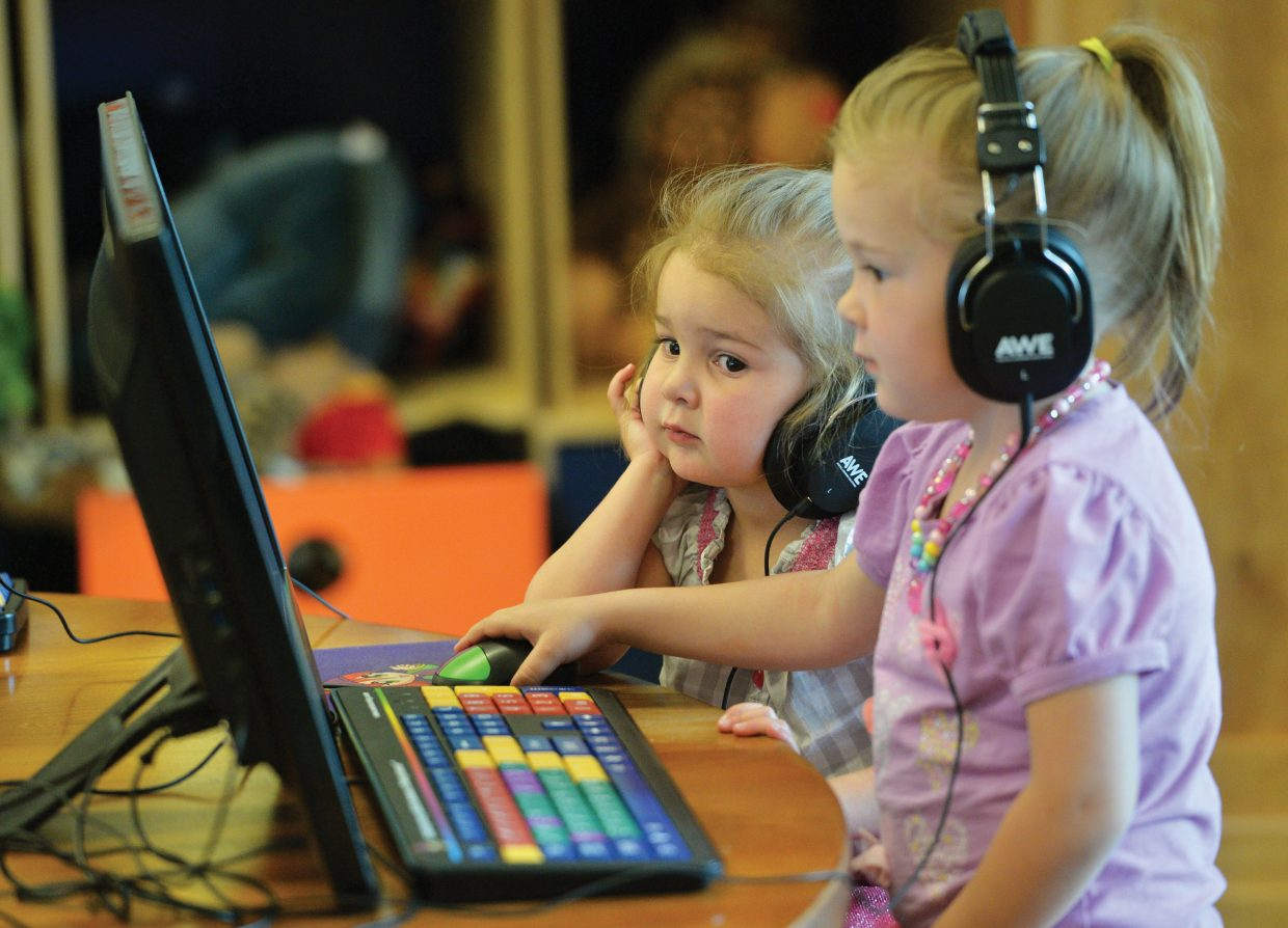 Genevieve Spillane watches as her older sister Hadley plays a game on the computer inside the children's area at the Bud Werner Memorial Library Monday afternoon.