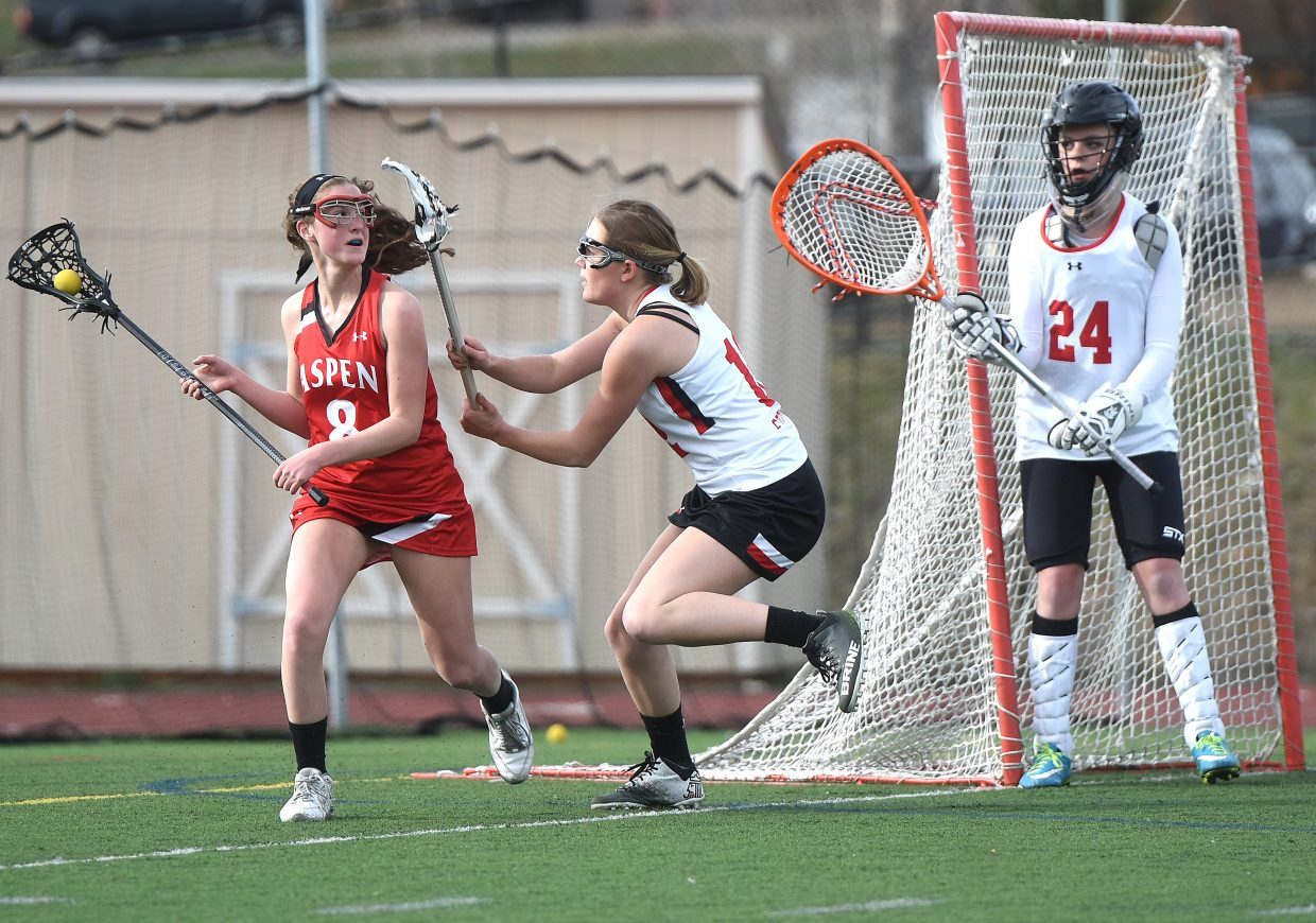 Aspen's Charlotte Howie looks for a way around Steamboat's Maura Glynn as goalie Ava Thiel watches on Thursday. The Skiers went on to win the game, 18-3, snapping Steamboat's five-game season-opening winning streak.
